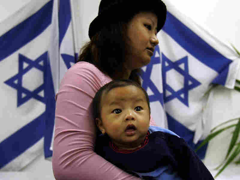 Arriving from India, a woman and her baby walk past  Israeli flags as they arrive in Israel