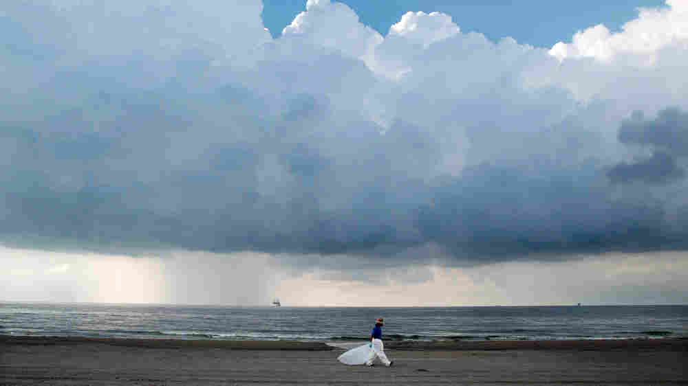 A worker leaves the beach as storm clouds approach Sunday in Grand Isle, La.