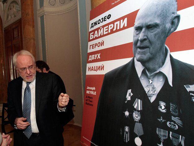 U.S. Ambassador to Russia John Beyrle attends the opening of the exhibition devoted to his father, Joseph R. Beyrle, seen in photo at right, in St. Petersburg, Russia, on Feb. 18. The exhibit is currently in Moscow.