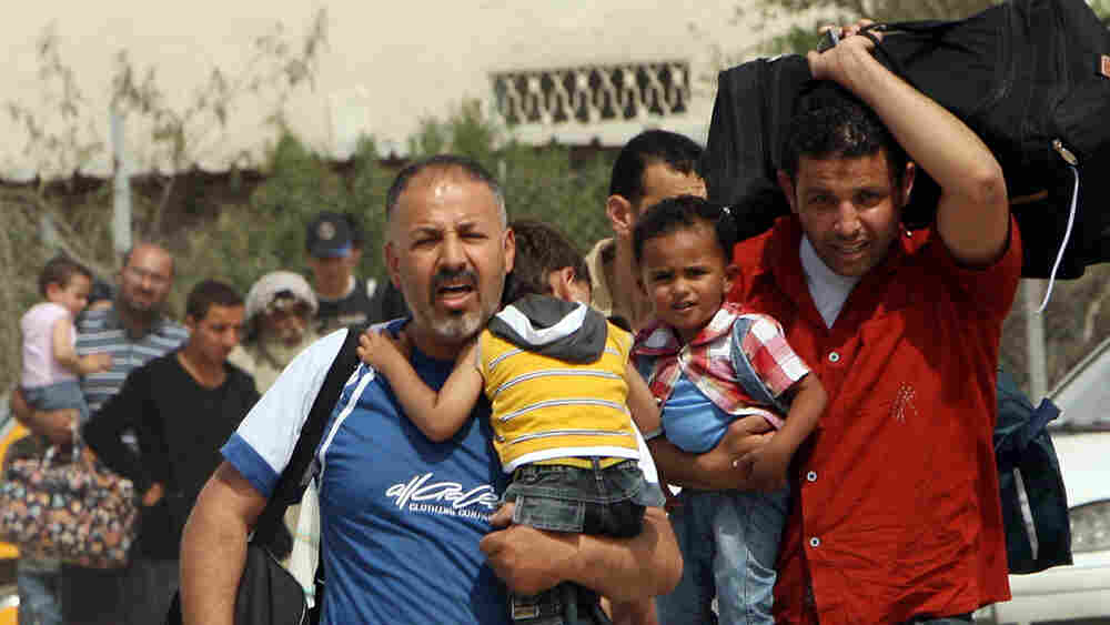 Palestinians carry their belongings as they head toward the Rafah border crossing with Egypt.