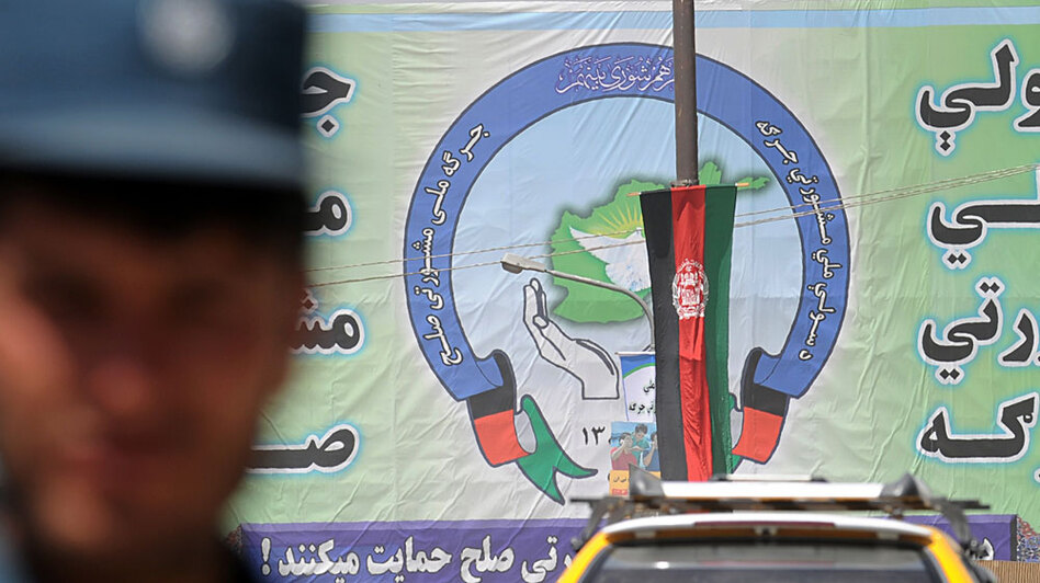 An Afghan policeman stands in front of a banner Monday advertising this week's gathering of Afghan tribal leaders in Kabul. The 1,600 delegates at the much-delayed and much-touted gathering will debate strategies for convincing the Taliban and other insurgents to lay down their arms.