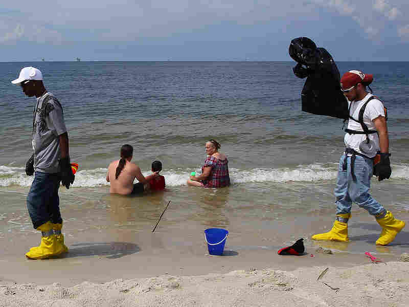 Workers hired to pick up oil walk past a family on the beach