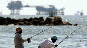 An oil drilling platform stands offshore in the Gulf of Mexico as people fish in Port Fourchon, La.