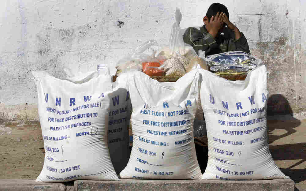 Palestinian boy with bags of flour at a U.N. food aid center in Gaza City
