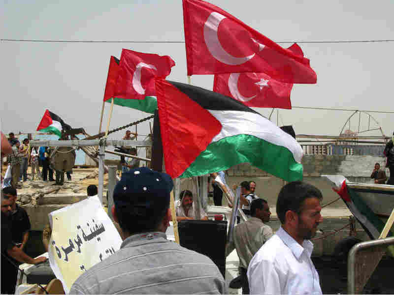 Turkish flags fly from Palestinian boats showing solidarity with Turkish activists.