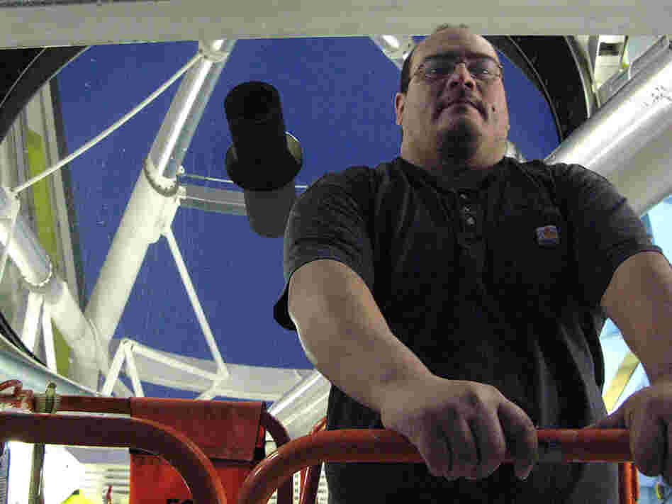 Michael Alegria with the Multiple Mirror Telescope he operates in Arizona.
