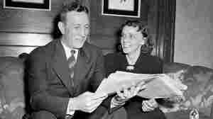 John Wooden looks at a newspaper with his wife, Nell, seated beside him on a sofa.