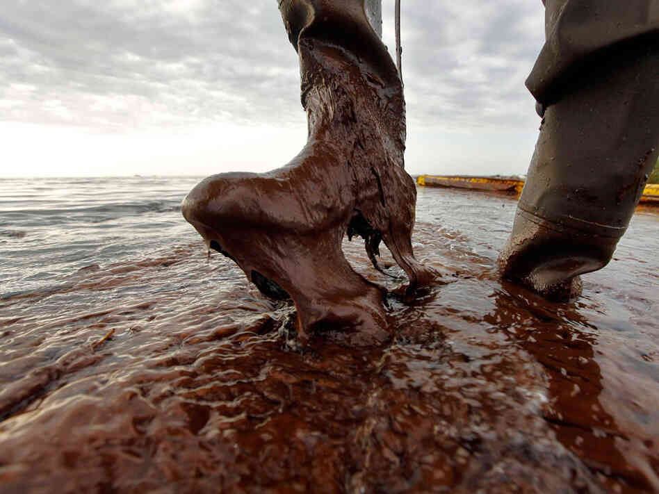 An official in Louisiana's Plaquemines Parish lifts his boot out of thick oil at Queen Bess Island.