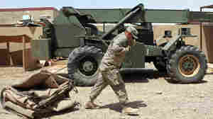A U.S. soldier drags a tent as his unit prepares to leave its base northeast of Baghdad.