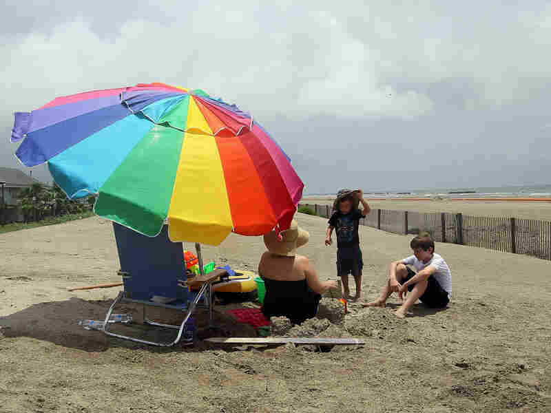 Beachgoers sit behind a fence prohibiting people from using the beach because of the spill.