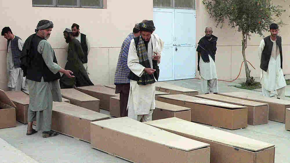 Afghan men inspect coffins of blast victims outside a hospital in Kandahar.