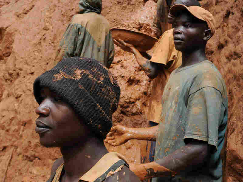 Gold miners on a muddy cliff in northeastern Congo.