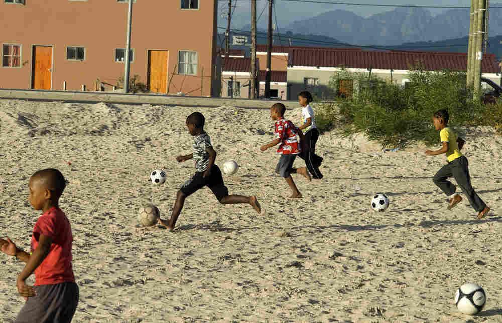 Children dribble soccer balls in Blikkiesdorp settlement outside Cape Town, South Africa, in April
