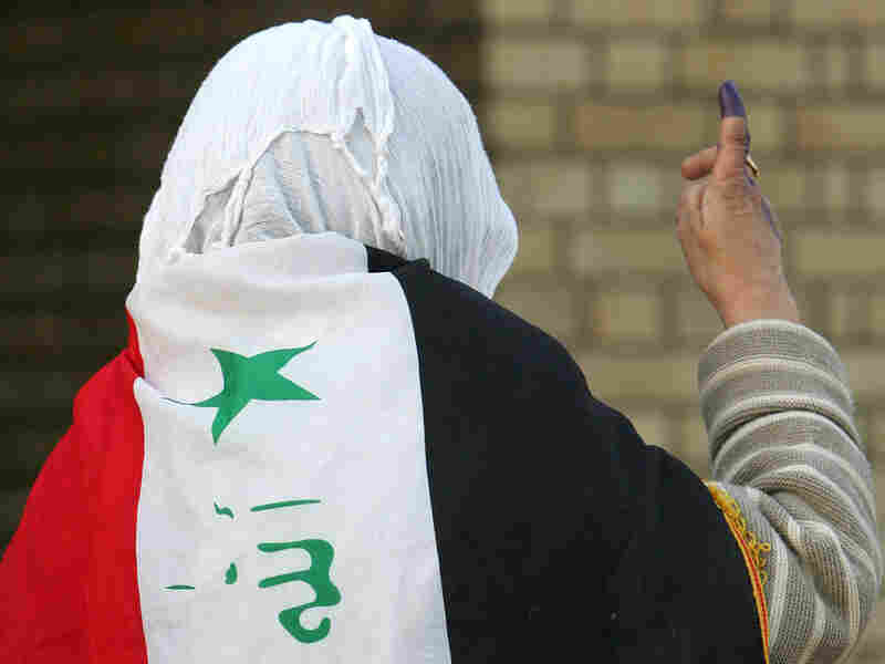 A woman wears an Iraq flag after voting in the country's parliamentary elections in March.