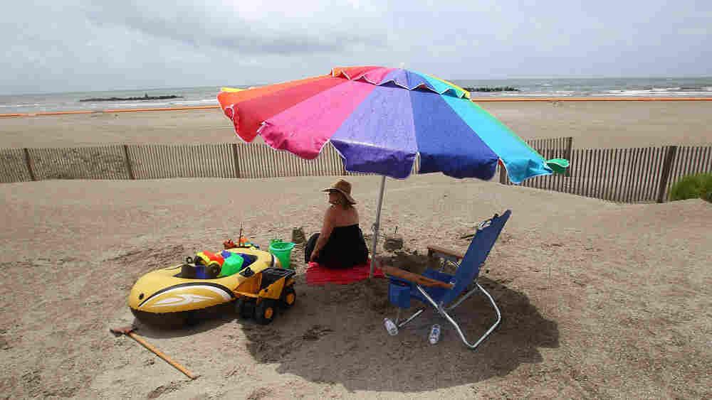 Millie Eichler sits behind a fence on a Louisiana beach.