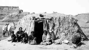 A Navajo family in front of a hogan in Canyon de Chelly in 1927.