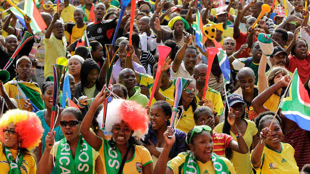 Soccer fans in Durban, South Africa, hold up their vuvuzelas