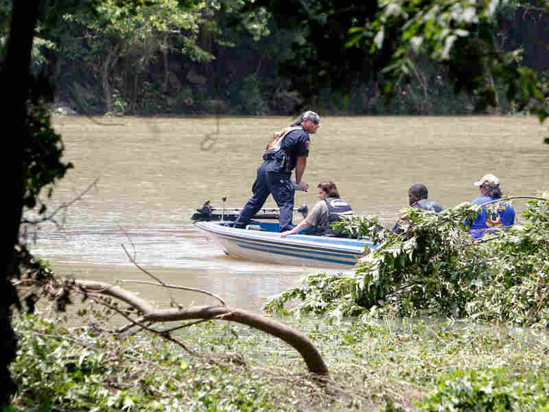 Officials search near the edge of the Little Missouri River near Langley, Ark.