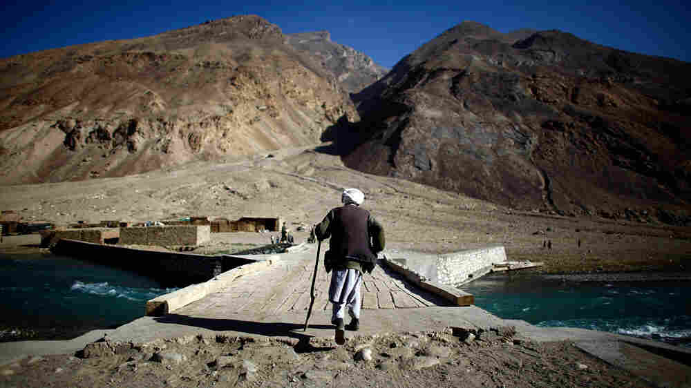 A man walks across a bridge over the Anjaman River in Afghanistan.