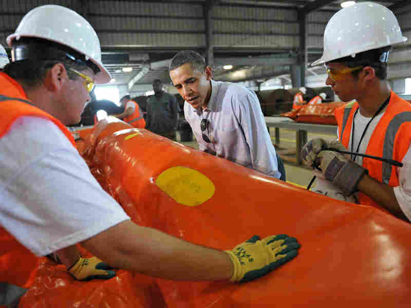 President Obama talks with workers repairing an oil boom in Theodore, Ala., on Monday.
