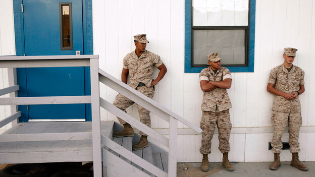 Three U.S. Marines waiting outside a building to take psychological tests