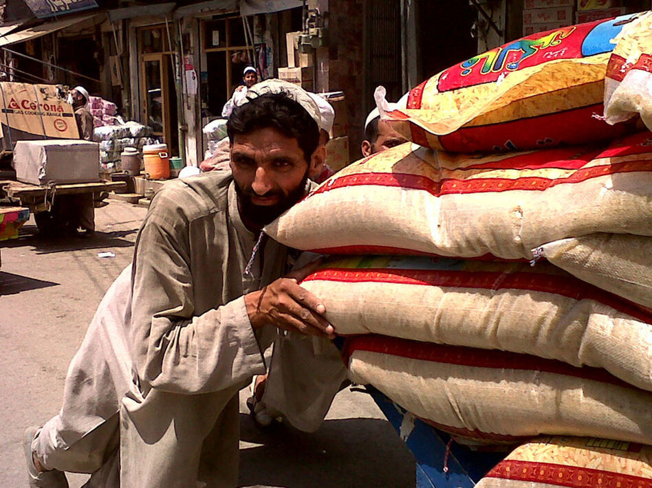 A man pushes a cart laden with sacks of grain through the streets of Swat Valley's main city Mingora. The Taliban terrorized the population and forced women to stay inside. Now, the markets are teeming again.