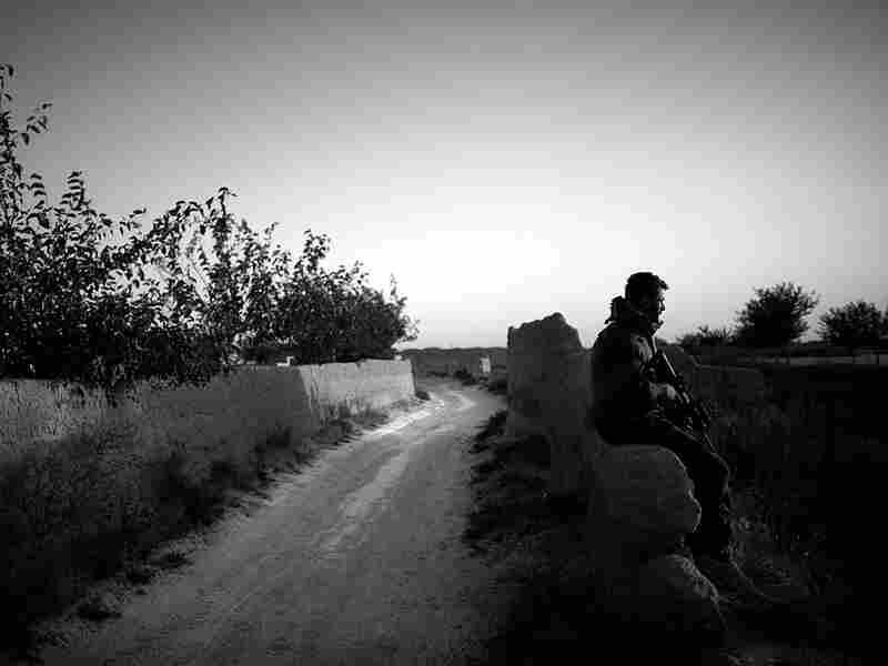 An Afghan commando sits on a mud wall