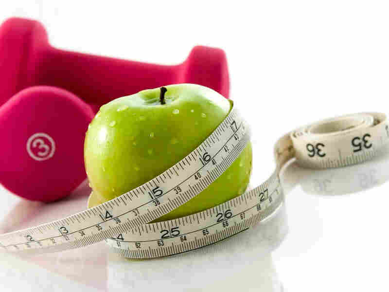 Fresh appetizing apple and brightly colored dumbbells tied with a measuring tape.