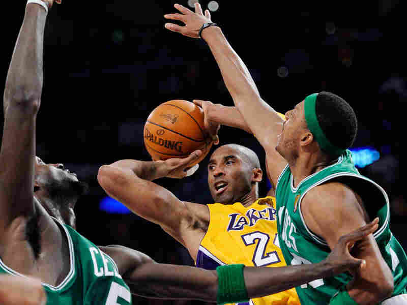 Lakers guard Kobe Bryant shoots around the outstretched arm of Celtics forward Paul Pierce.