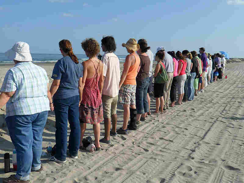 Following an interfaith service, people gather at a berm overlooking the ocean and hold hands.