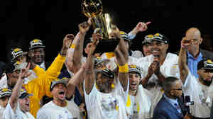 The Lakers hold the trophy overhead, celebrating Thursday's NBA championship win over the Celtics.