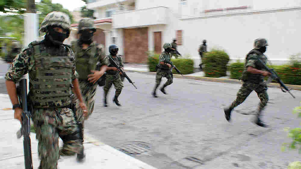 Mexican navy marines run down a street after a gun battle erupts in Acapulco.