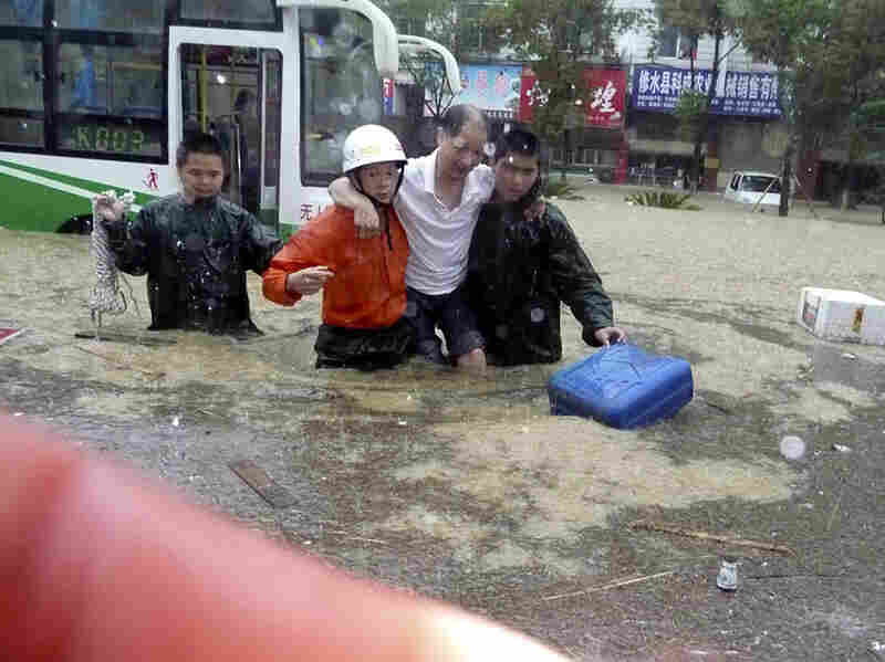 Chinese firemen evacuate a man trapped in the floods in central China