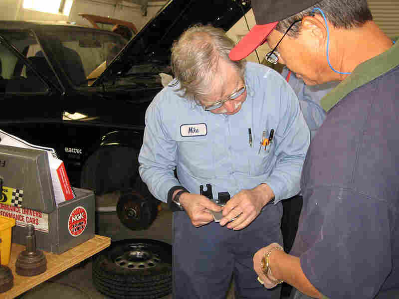 Mike Brown (left) helps Daniel Marcom with his gas-to-electric car conversion.