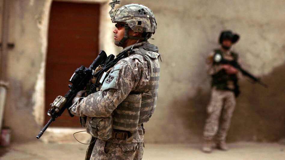 An Iraqi army soldier and a U.S. Army soldier stand guard during a joint patrol in Mosul in March 2009.
