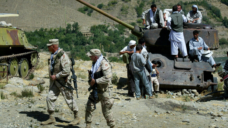 Two U.S. soldiers walk past a group of Afghan men resting on top of a destroyed tank in the Panjshir Valley of Afghanistan in September 2005.