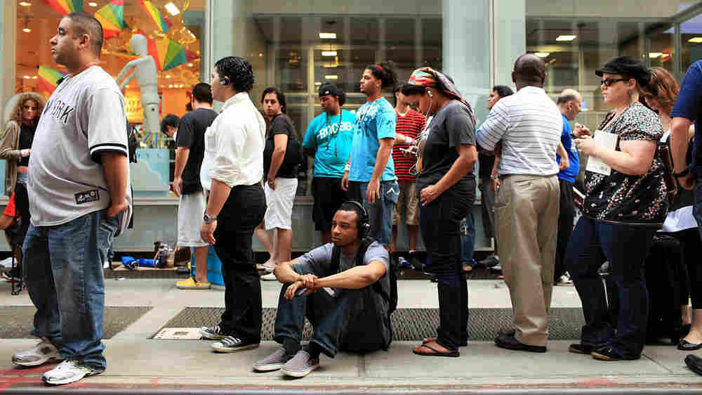 Customers wait in line for the new iPhone 4 at the Apple Store on Fifth Avenue in New York City.