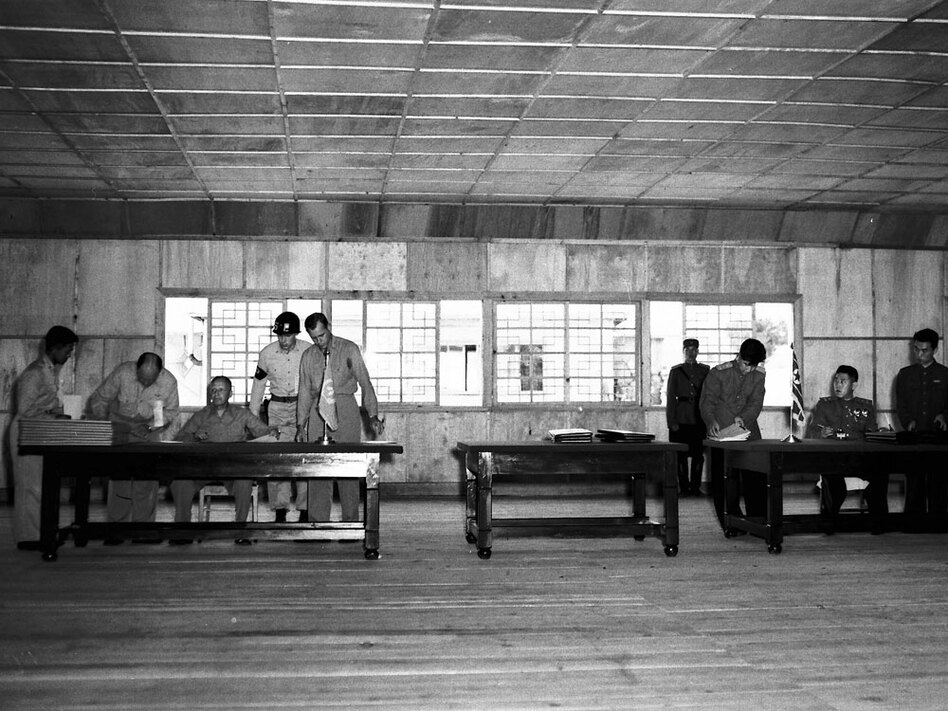 Gen. William K. Harrison, Jr., seated at left, and North Korean Gen. Nam Il, seated at right, sign armistice documents in Armistice Hall in Panmunjom, a no man's land between the Koreas, on July 26, 1953. (AP)