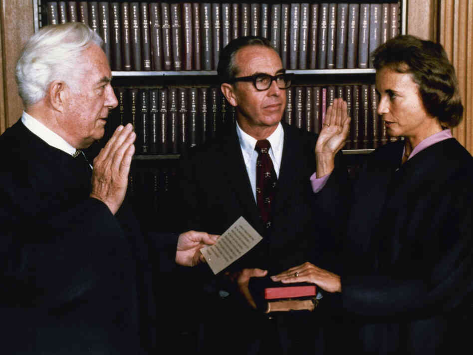 Justice O'Connor, right, is sworn in by Chief Justice Warren Burger, left, with her husband.