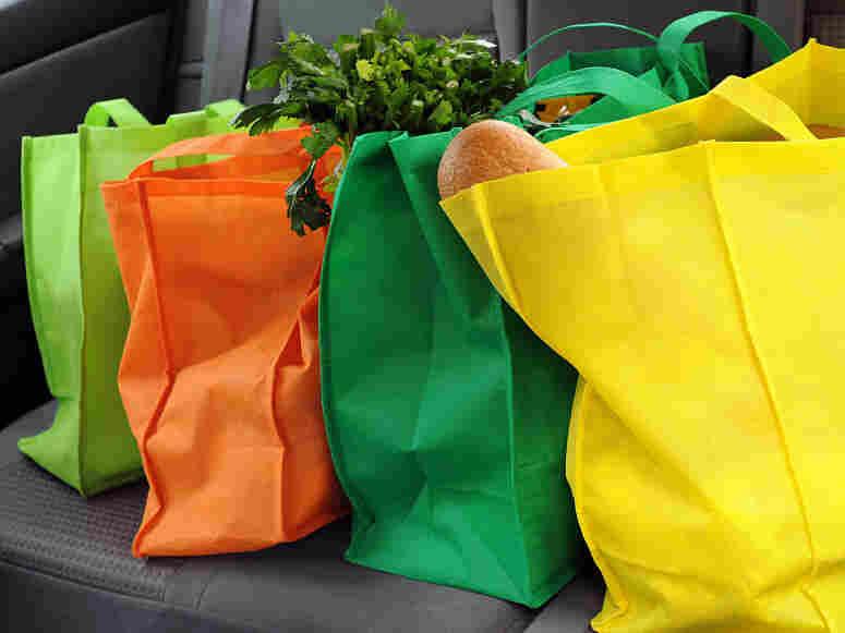 Reusable grocery bags on a shelf.
