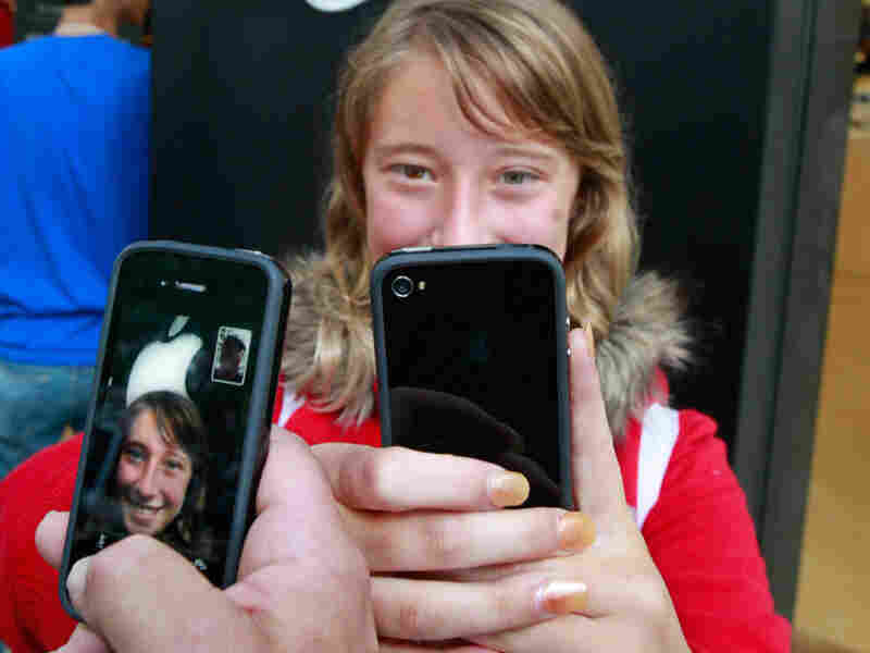Emilie Weideman and her father, Marc Weideman try their new iPhones Thursday in Palo Alto, Calif.