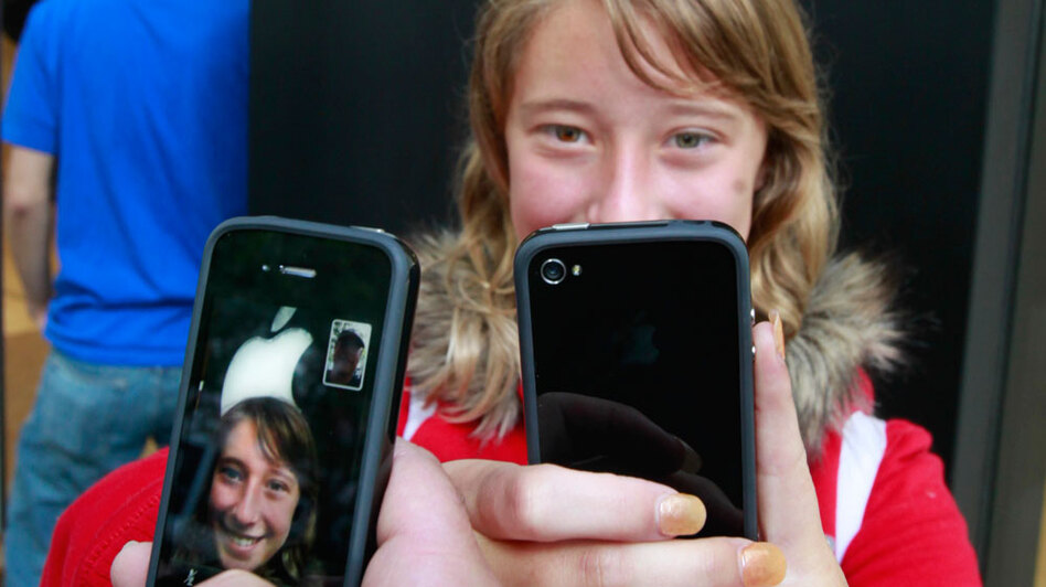 Emilie Weideman and her father, Marc Weideman try their new iPhones Thursday in Palo Alto, Calif. Many of the new phones' owners are complaining of a glitch that drops calls.