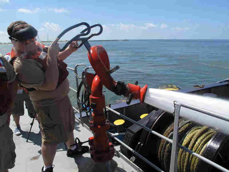 John Meaut aims a spray nozzle at a ship. Debbie Elliot/NPR