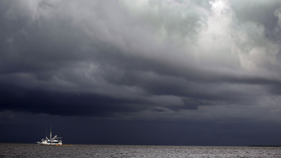 The looming storm could postpone BP's plans to double the amount of oil they capture from the spill. Here, a boat uses a boom and absorbent material to soak up oil on the surface of the water near Grand Isle, La., on Monday.
