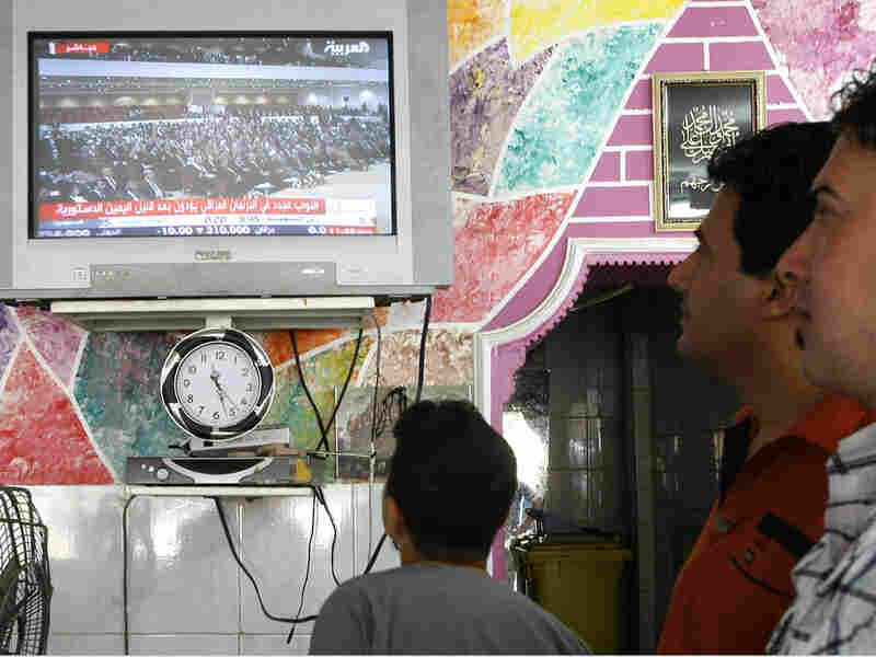 Iraqis follow a parliamentary session on local TV at a barbershop in Baghdad