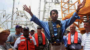 Gov. Bobby Jindal talks to fishermen and workers helping to clean up the BP oil spill on a boat.