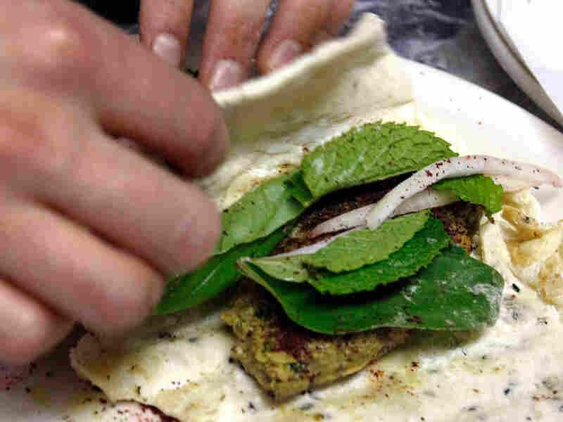 Lucy Wang rolls up an Iranian kubideh wrap sandwich in the prep area.