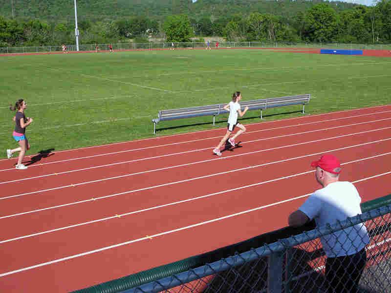 Stevens High School track athletes run in a public park near the school.