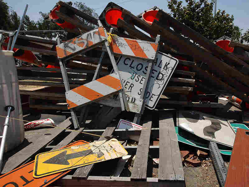 Road and construction signs lay in a pile in Maywood, Calif.