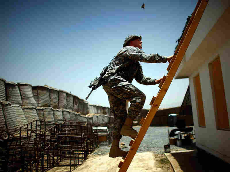 Lt. Col. Johnny Davis climbs on to the roof of a building